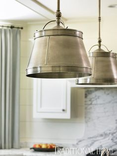 """DeLoach intentionally mismatched finishes—polished nickel faucets, antiqued nickel light fixtures, and hammered pewter pulls on cabinets. """"I love for things to look collected, not like they all came out of the same store,"""" she says.  Antiqued nickel pendants above the island and wall sconces are from Circa Lighting."""