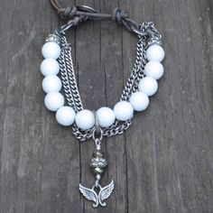 Boho Chic Handmade Faceted Agate Bead Chain and Leather Charm Bracelet made with faceted white agate gemstone beads patina silver crystal rondelles placed at each end hanging at center is a handmade pyrite, crystal rondelle and silver angel wing charm antique silver curb chain sterling silver ornate bird button closure grey natural leather measures 7.25 from button to closure.