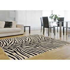 This traditional ivory area rug features a design that will revitalize a room in your home. This abstract, contemporary rug is ivory and black in a groovy animal print. This large polypropylene rug measures 90 inches by 118 inches.