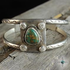 This beautiful bracelet features a simple shank cuff and square silver pendant centered with an old green turquoise stone. Hand stamped silver buttons accent the stone. The stone measures about 1/2″ in diameter. Cir. 1960s