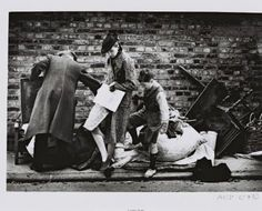 1940. A London family bombed out of their home during the night, salvage a few personal belongings on the pavement | Arts Council Collection