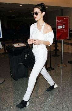 Bella Hadid wears a white tracksuit, white tank, black handle bag, and black Adidas sneakers.