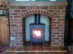 Clearview Pioneer multifuel stove in brick-arch fireplace.