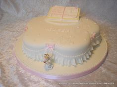 Petal communion cake finished with a garret frill pink sugar hearts and topped with sugar open pray book and kneeling communion modelled girl