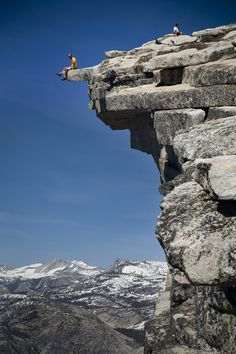 "Climber sits on the edge of ""The Diving Board"" atop Half Dome in the Yosemite Valley."