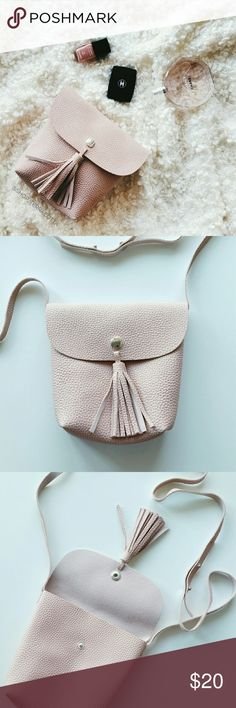 """Vegan Leather Tassel Crossbody Bag - Baby Pink Vegan Leather Tassel Crossbody Bag  *Baby pink pebble textured vegan leather  *One Size - 7""""?6.5""""?2.5"""" *Adjustable shoulder straps - 47""""-52.5"""" *Great for carrying your essentials. Would fit a little wallet, cell phone and few small makeup items. *New boutique item - No tags  *No trade shop_terracotta Bags Crossbody Bags"""