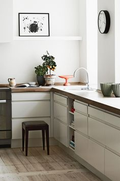 white | west coast | wooden counter | natural | floor detail | square hood fan cover | open shelf | artwork in the kitchen | minimal