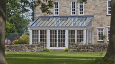 Traditional lean-to conservatory measuring 6.5m x 3.8m with slender timber columns and 12 pane window design.