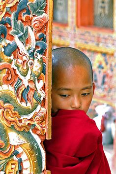 Bhutan, Paro, shy young novice Buddhist monk dressed in the traditional red dress standing beside a heavily decorated and painted pillar from  Anthony Asael