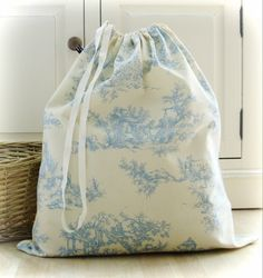 A classic French Toile de Jouy design cotton laundry bag in a blue on cream colourway. The top of the laundry bag has a drawstring tape and the bag is approximately 54cm wide and 62cm long offering plenty of space for your laundry. Double stitched French seams for durability.