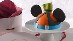An Amorette's Patisserie Goofy dome cake on a pedestal next to its hat box packaging