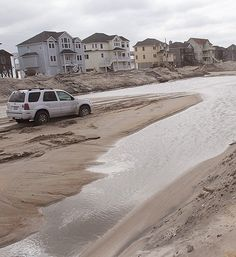An SUV is stuck in the sand on NC 12 in the Mirlo Beach area of Rodanthe, N.C. on Thursday, March 7, 2013, the day after a winter storm brought sound-side flooding and some ocean overwash to Hatteras Island