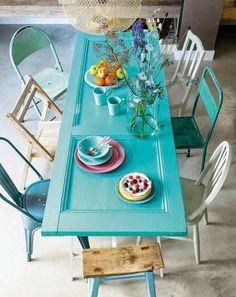 Una de las opciones más interesantes es la de convertir esta puerta en mesa. Podemos usarlas en cocinas y comedores, dependiendo de su tamaño. Son ideales, pues pueden pintarse de cualquier color. Tan sólo necesitaremos unas patas, que perfectamente pueden ser caballetes, y unas cuantas sillas. Y si deseamos innovar, podríamos añadirle sillas diferentes, para darle más dinamismo.: