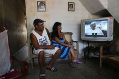 People watch as Pope Francis is shown on television as he arrives in Havana, Cuba on September 19, 2015 in Santiago de Cuba, Cuba. - © Joe Raedle/Getty Images