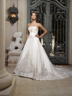 Silky Taffeta gown with Swarovski crystals, pearls, rhinestones, silver beadwork and embroidery sewn onto blush netting. Neckline is straight across and strapless and the silhouette is ball gown.