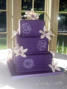 The cake is covered in a purple fondant, decorated with brushed embroidery flowers and additionally with sugar Cymbidium orchids.