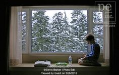 7-year-old Canadian boy kneeling in the window sill in his hotel room writes in his notepad, Whistler, British Columbia, Canada