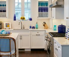 The different shades of blue in this beach house kitchen bring the white cabinets to life and remind us of the ocean just outside the window.