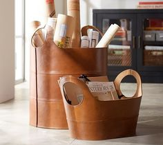 "$149-$229 Hayes Leather Storage Baskets | Pottery Barn - low/tote sz could be for living room.  LG/round one could be for fireplace wood leave by the fire? Or even laundry basket, or like they are using it for architectural drawings in study.  Low oval:  22""L x 12""w x 8""ht. Floor:  18""diameter x 18""ht. (larger)"