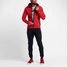 Il porte un t-shirt gris, un pull rouge, des pantalons de survêtement et des baskets rouges.