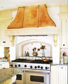 Detailed tile trim and decorative corbels support a French-style copper range hood.