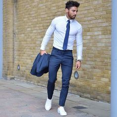 Acheter la tenue sur Lookastic: https://lookastic.fr/mode-homme/tenues/costume-bleu-chemise-de-ville-blanche-tennis-blancs/20358 — Chemise de ville blanche — Cravate á pois bleu — Costume bleu — Tennis blancs