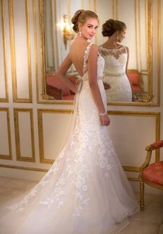 "This Lace and Tulle fit-and-flare designer gown from the Stella York collection features an illusion Lace bateau neckline, fitted Lace bodice and flowy Tulle skirt and court train. The back zips up under sparkling crystal buttons. Detached beaded 1"" Valencia Satin ribbon sash included."