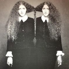Two young woman (twin sisters?) with their hair braided together. (original source unknown)