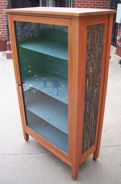 """A Display Cabinet / Curio Cabinet.  By Mike Squared Mosaics. The Mosaic is vertically placed rectangular Slate Tile. A large Glass pane front.  All four sections have been electrically lighted for an illuminating night time display. The measurements are as follows:  32"""" wide x 56"""" high x 14.5"""" deep.  The shelves are 12"""" deep. This Cabinet is for sale at our Workshop in Denver. Call 303-657-0261.  $800.00. We accept all Major Credit Cards. Visit our website at…"""