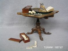 https://flic.kr/p/Besunc   Doll's house side table and accessories, about 1840   Side table and dominoes from Rigg Doll's House, about 1840 On display at Tunbridge Wells Museum & Art Gallery.