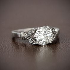 A gorgeous Antique Engagement Ring set with a stunning old mine diamond and accented with diamond studded leaves on either side. The