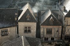 Time freeze - smoke rises from the ancient chimneys of houses in the medieval french village of Saint Cirq Lapopie