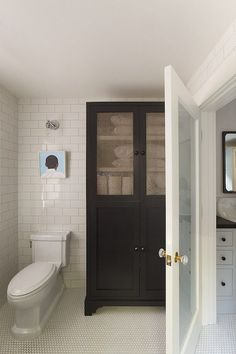 Fantastic bathroom features frosted glass water closet door opening to floor to ceiling subway tiled walls framing art over toilet next to freestanding black linen cabinet accented with metal mesh doors.