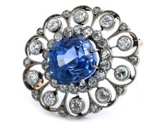Sapphire and diamond brooch Length: ca. 3 cm. Weight: ca. 6.3 cm. Platinum on 14 ct yellow gold. Ca. 1910. Fine antique brooch in blue-purple, oval facetted Ceylon sapphire, ca. 7.7 ct, with a surround of old-cut diamonds, altogether ca. 1.8 ct.