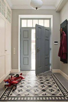 Przedpokój ze stylową białą szafą i nowoczesnym wieszakiem na okrycia wierzchnie zdobi wzorzysta podłoga. Gładki szary gres połączono ze spektakularnymi cementowymi kaflami w eleganckie wzory. Bordiura w romby sprawia, że część posadzki wygląda jak dywan.