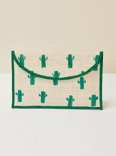 """Going on vacation? Take me with you. This is a straw clutch with hand embroidered cacti and a gold clasp. KAYU bags are carefully handcrafted by women in the Philippines, Indonesia and Malaysia, preserving their indigenous crafts as well as providing them with a living wage.   Measurements: Width: 11"""" Height: 7"""""""