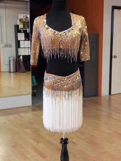 Two-piece tan latin dress with extensive stoning and fringe. Visit http://ballroomguide.com/comp/attire/lady.html for more info about competition attire.