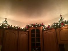 This is my actual kitchen: 12 ft Garland and white lights with apple ornaments and mini trees with gingerbread cookie theme ornaments on top of my kitchen cabinets.  Controlled by remote or I can set it to a timer.  We leave it up through Valentines Day because I love it so much.