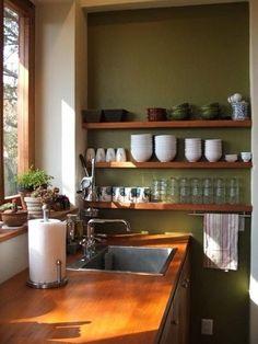 Open shelving, avocado green walls, restaurant style crockery & glassware, wood counter tops