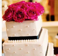 The cake, a four-tiered, square confection with alternating layers of fresh strawberries and lemon filling, was showcased at the reception. The stacked cake was decorated with white buttercream and a black ribbon of icing around the bottom of each tier. T...