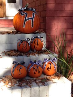 """Made these for the Fall season. The large pumpkin is a carving one and the others are all pie pumpkins. The initials are monogram stickers and I made the bows and hot glued them on. Of course making the ribbon for the """"T"""" for my daughter pumpkin a little different that the ribbon for the boys."""