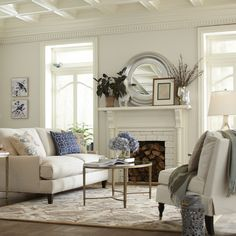 Mantle styled with round mirror, layered art, and accessories