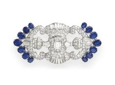 A DIAMOND AND SAPPHIRE BROOCH   Designed as single and circular-cut diamond openwork plaque, centering upon a rectangular-cut diamond with collet, shield and baguette-cut geometric detail, framed by oval-cut sapphires, mounted in platinum