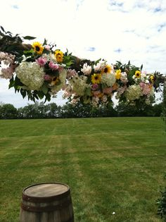 Beautiful sunflower, rose and hydrangea floral arch for a Kentucky outdoor wedding by Fields in Bloom