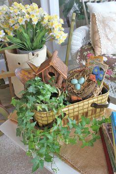 Vintage picnic basket vignette - nest, seed packets, birdhouse, ivy, garden tools.