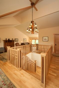 Completed custom home interior, second floor wood railing with stairway leading to first floor. Louden Ridge of Saratoga Springs, NY