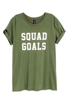 Camiseta con motivo estampado: Camiseta en punto suave de algodón con motivo de texto delante y dobladillos cosidos vueltos en las mangas.