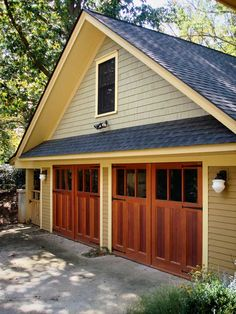 The new garage for a 1902 Shingle Style house in North Carolina has  custom-made doors in an Arts u0026