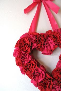 """Description:This tutorial will guide you through the steps to make a Fabric Flower Valentine Wreath. Beginner sewing skills are required, and anyone from a new crafter to a """"Martha"""" will enjoy this project. Materials Needed:Sewing machine and threadGlue gun and 8-12 glue sticks1 yd 45″ wide red broadcloth1 yd 45″ wide pink broadclothHeart shaped floral …"""