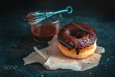 Chocolate donut with sprinkles on dark background with a whisk and chocolate glazing. Low key... by Dina (Food Photography) on 500px